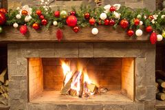 New Year / Christmas tree with colorful festive decorations on the fireplace Royalty Free Stock Photos