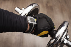it's time to start fitness. The man's hand in a glove with a dumbbell Royalty Free Stock Images