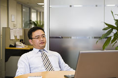 It's time to stop and think. Asian business executive doing some thinking in his office Stock Photos