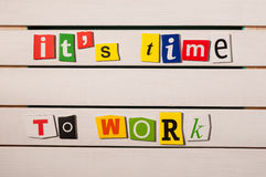 It's time to work - written with color magazine letter clippings on wooden board. Concept  image.  Royalty Free Stock Photo