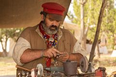 An 1800`s tinker in a mountain man festival files the edge of a copper trinket stock photography