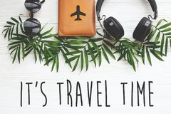 It`s Travel Time text on passport with plane, retro sunglasses a. Nd headphones on green palm leaves on white wood. modern travel and summer vacation flat lay Stock Image