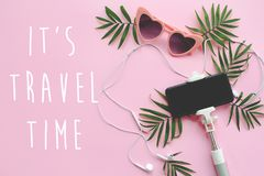 It`s Travel Time text on stylish pink sunglasses, phone on selfi. E stick, headphones, and green palm leaves on pink background. summer vacation flat lay. time Stock Image