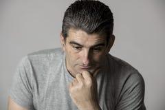 40s a 50s triste e ao homem preocupado que olha frustrado e pensativo na expressão preocupada e pensativa da cara isolada no cinz Foto de Stock