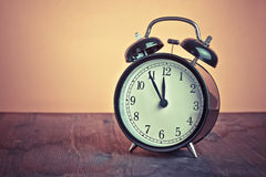 It`s twelve o`clock already, time to wake up for lunch, vintage old black metallic alarm clock Royalty Free Stock Image