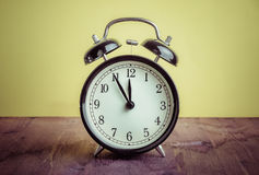 It`s twelve o`clock already, time to wake up for lunch, vintage old black metallic alarm clock Royalty Free Stock Photos