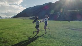 Trendy Hipster Girls having fun outdoor. Three cute women are whirling on green grass. Best friends. 20s Two girlfriends are exchanging a circle in a sunny stock footage