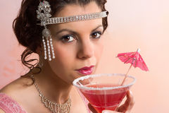 1920s vintage woman with cocktail. Beautiful young vintage 1920s woman with headband and flapper dress drinking a cocktail royalty free stock photos