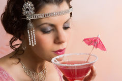1920s vintage woman drinking. Beautiful young vintage 1920s woman with headband and flapper dress drinking a cocktail stock image