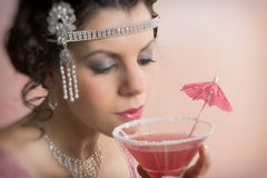 1920s vintage woman drinking cocktail. Beautiful young vintage 1920s woman with headband and flapper dress drinking a cocktail Royalty Free Stock Photos