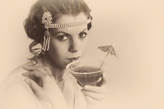 1920s vintage woman in sepia. Beautiful young vintage 1920s woman with headband and flapper dress drinking a cocktail royalty free stock photography