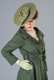 Forties vintage vogue style high fashion woman. 40s vogue style beauty model in vintage green hat and coat Royalty Free Stock Photos