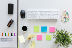 It's a well organized desk!. White desk with keyboard, colorful paper clips and sticky notes - view from above Stock Photography