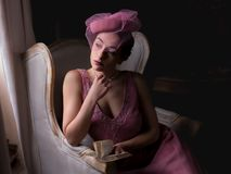 1920s woman backlit. Attractive young woman in 1920s flapper dress sitting in dark room near windows, with clair obscur light effect royalty free stock photography
