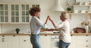 Elderly woman dancing with grown up adult daughter in kitchen