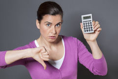 30s woman disappointed by figures shown on her calculator Stock Image