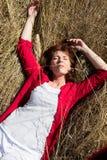 50s woman enjoying sun warmth alone sleeping on dry grass Royalty Free Stock Image