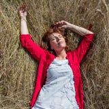 50s woman enjoying sun warmth sleeping alone on summer grass. Sun warmth wellbeing - gorgeous aging woman enjoying sunbathing, lying alone in a summer grass stock photo