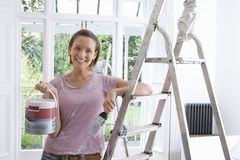 20`s woman home decorating indoors with paint, brush and ladder ,. 20`s women home decorating indoors with paint, brush and ladder stock photos