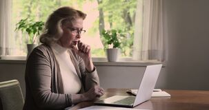Elderly woman using laptop experiences problems with device feels angry