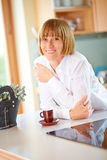 40s woman at the kitchen with cup of coffee Royalty Free Stock Photo