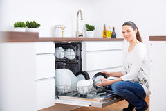 20s woman in kitchen, empty out the dishwasher 3 Stock Photos