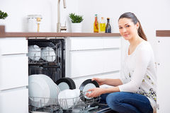 20s woman in kitchen, empty out the dishwasher 6 Royalty Free Stock Images