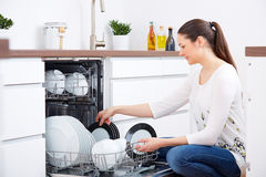 20s woman in kitchen, empty out the dishwasher. Modern ambiance Stock Photography