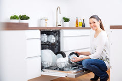 20s woman in kitchen, empty out the dishwasher 2 Stock Photos