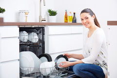 20s woman in kitchen, empty out the dishwasher 5 Stock Photography