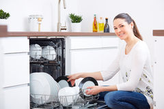 20s woman in kitchen, empty out the dishwasher 4 Stock Photos