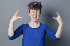 30s woman shouting with hard rock hand gesture. Optimism concept - stylish 30s woman shouting with hard rock hand gesture for rebellion or bold success, studio Royalty Free Stock Photos