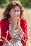50s woman sneezing for rhinitis,allergies or hay fever. Outdoors illness - beautiful 50s woman sneezing for rhinitis,allergies or hay fever reaction,summer Stock Images