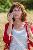50s woman suffering from rhinitis or hay fever outdoors. Outdoors illness - beautiful 50s woman with freckles suffering from headache, rhinitis or hay fever Royalty Free Stock Photo