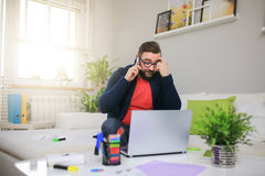 It's worth to think it over. A photo of young man discussing something over the phone. He's working at home Stock Photos