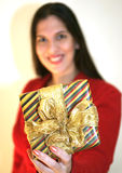 That's for you!. A smiling young woman in a red sweater offering a wrapped gift with a golden ribbon. note that the focus is on the gift, the woman is out of stock image