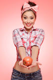 It's for you!. Sexy young pin-up girl stretching out her hands holding an apple Royalty Free Stock Image