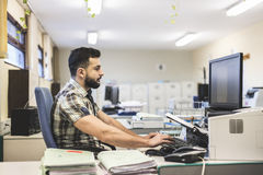 30s young hipster man style working. At office with ambient light Stock Image