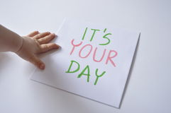 IT'S YOUR DAY. Paper with inscription: IT'S YOUR DAY, with child's hand Stock Image