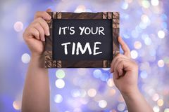It`s your time. A woman holding chalkboard with words it`s your time on bokeh light background Stock Images