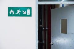 A saída de emergência assina dentro a maneira da saída de emergência do terminal de aeroporto Thaila fotografia de stock royalty free