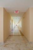 A saída de emergência assina dentro o corredor Imagens de Stock Royalty Free