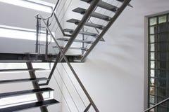 Saída de emergência por um vão das escadas em um edifício moderno Foto de Stock
