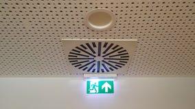 A saída de emergência verde pequena assina no escritório fotografia de stock