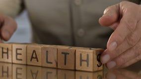 Saúde, ancião que faz a palavra de cubos de madeira, reforma médica, pontas dos cuidados médicos filme