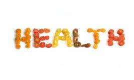 A saúde da palavra escrita nas fatias de tomates de cereja Fotos de Stock Royalty Free