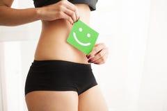 Saúde das mulheres Close up da fêmea saudável com corpo magro apto bonito na cuecas preta que guarda o cartão verde com feliz foto de stock
