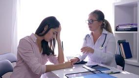 A saúde das mulheres, doutor vê o raio X à disposição e apoia então o paciente da mulher no escritório médico filme