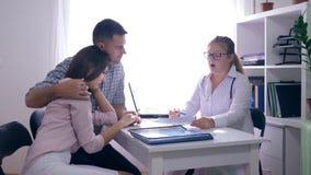 Saúde das mulheres, fala do doutor do ginecologista da infertilidade a um par novo da virada no escritório médico branco no hospi video estoque