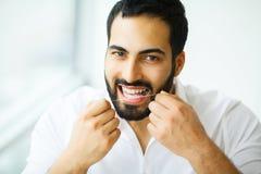 Saúde dental Homem com o sorriso bonito que Flossing os dentes saudáveis fotos de stock